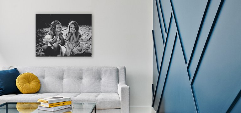 A canvas print hanging above a couch next to an accent wall.