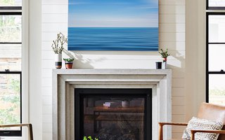 A canvas print above a fire place.