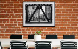 A framed print positioned above a meeting room table.